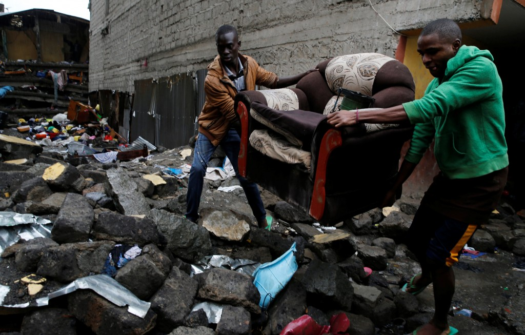 People carry a sofa as they leave the Huruma neighbourhood during the search for residents feared trapped in the rubble of a six-storey building that collapsed after days of heavy rain, in Nairobi, Kenya May 1, 2016. REUTERS/Thomas Mukoya