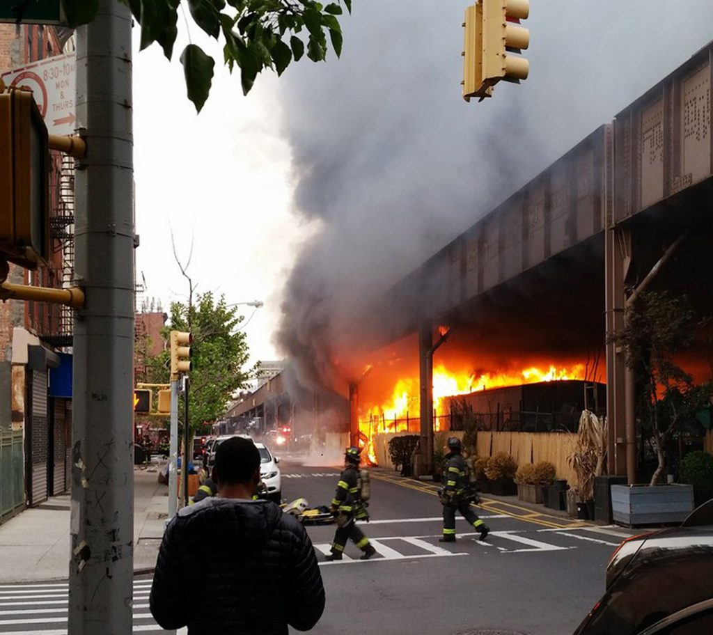 Firefighters on Tuesday night battle a blaze at the Metro-North tracks in East Harlem.(Benjamin Parkin via AP)