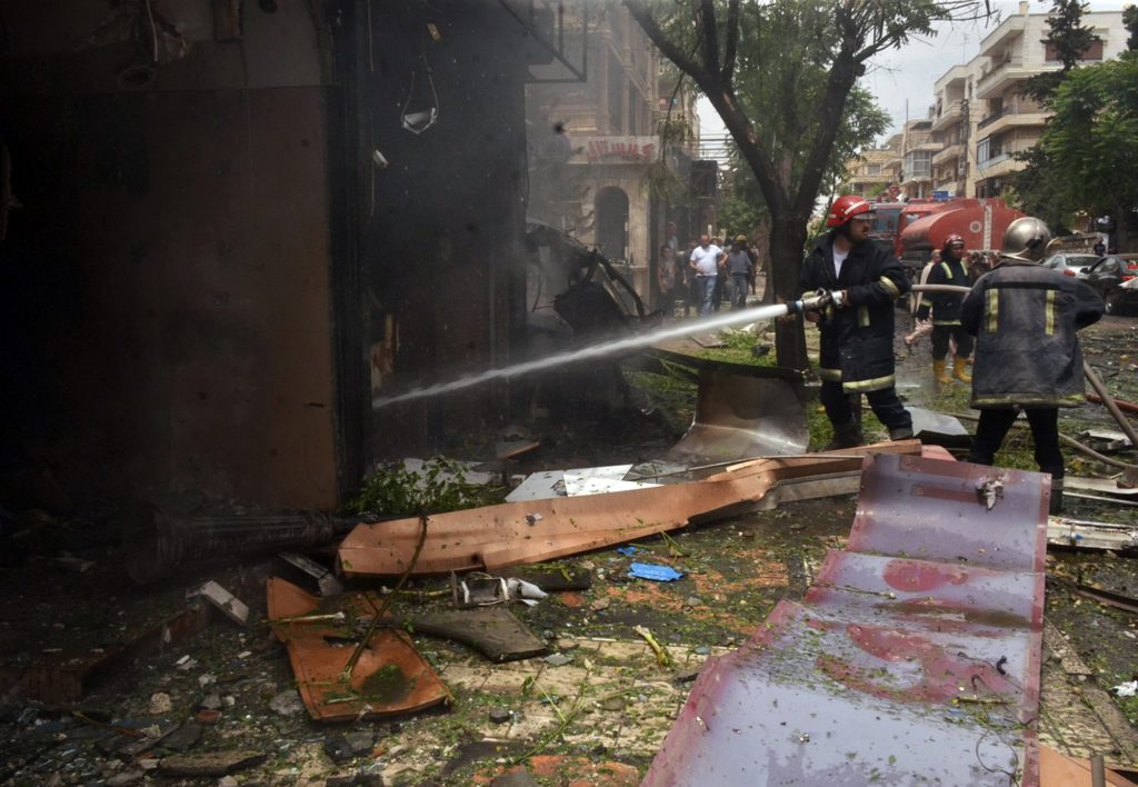 FILE - In this Tuesday, May 3, 2016 file photo, released by the Syrian official news agency SANA, Syrian citizens and firefighters gather at the scene where one of rockets hit the Dubeet hospital in the central neighborhood of Muhafaza in Aleppo, Syria. As one of the few pediatricians remaining in the Syrian city Aleppo, Dr. Mohammed Wassim Maaz was the last ray of hope for tens of thousands of children and their parents trapped in the horror and misery of the five-year civil war. (SANA via AP, File)