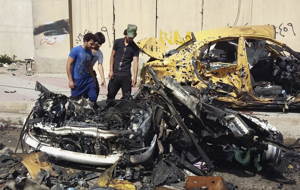 Citizens inspect the scene after a parked car bomb went off in Baghdad's southwestern Saydiyah neighborhood on Monday, killing and wounding scores of Shiite pilgrims who were commemorating the anniversary of the death of a revered imam. (AP Photo/Assad Muhsin)