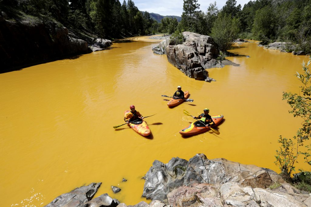 In this Aug. 6, 2015 photo, people kayak in the Animas River near Durango, Colo., in water colored from a mine-waste spill. (Jerry McBride/The Durango Herald via AP, File)
