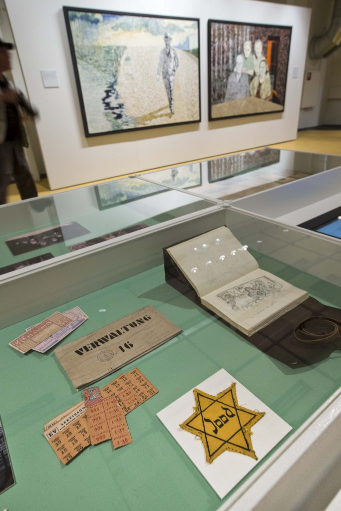 The Jewish star badge worn by the grandmother of Dutch actor and artist Jeroen Krabbe and some of Krabbe's paintings are displayed during a press preview at the National Holocaust Museum in Amsterdam, Netherlands, Thursday, May 12, 2016. (AP Photo/Peter Dejong)