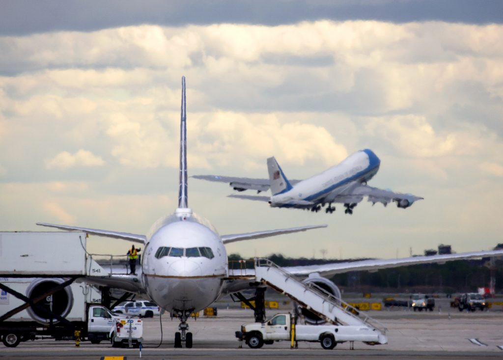 Seen though exhaust from aircraft on the ground, Air Force One with President Barack Obama aboard takes off from Newark Liberty International Airport in Newark, N.J., Sunday, May 15, 2016. Obama earlier delivered a commencement address at Rutgers University. (AP Photo/Craig Ruttle)