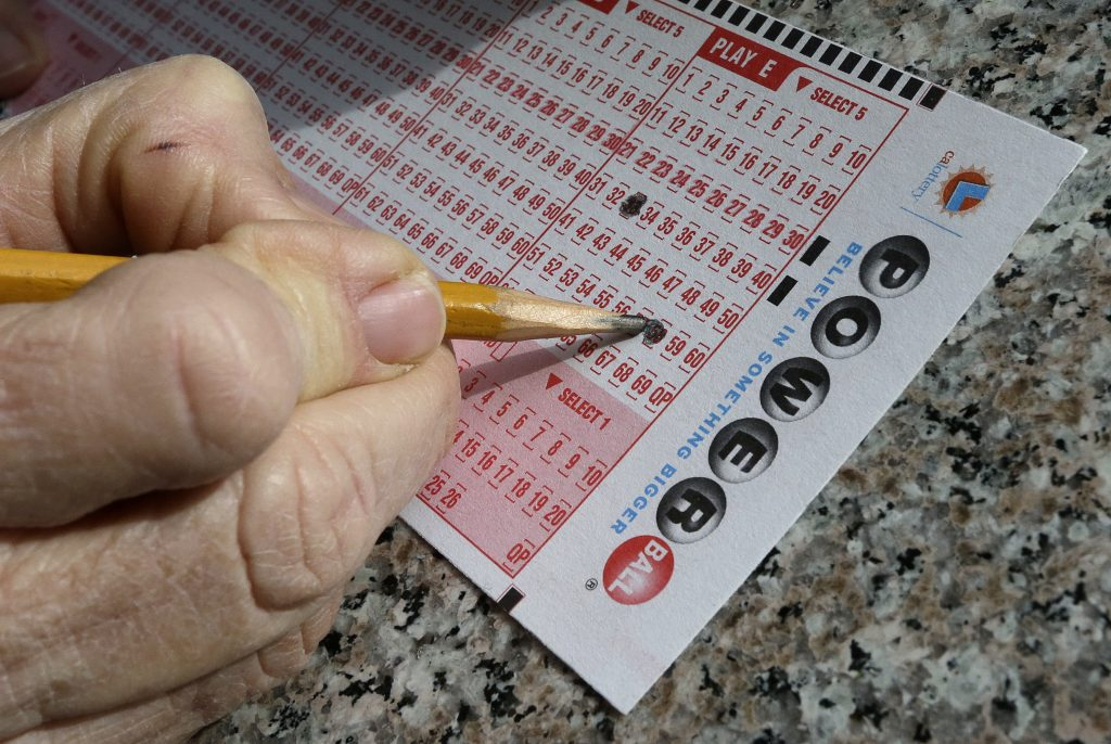 FILE - In this Jan. 12, 2016 file photo, a lottery player fills out numbers on a powerball form in Oakland, Calif. The Powerball jackpot has grown to over 1.5 billion dollars. Only ne ticket matched all six numbers in the drawing Saturday, May 7, for a $429.6 million jackpot, said Powerball spokeswoman Kelly Cripe, and New Jersey lottery officials said Sunday it was sold at a 7-Eleven store in Trenton, N.J. (AP Photo/Ben Margot, File)
