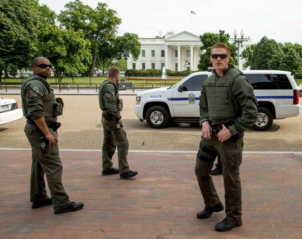 Law enforcement officers stand on Pennsylvania Avenue in front of the White House in Washington, Friday, May 20, 2016, after the White House was placed on lockdown for a shooting nearby. A U.S. Secret Service officer shot a man with a gun who approached a checkpoint outside the White House on Friday afternoon and refused to drop his weapon, the Secret Service said. (AP Photo/Andrew Harnik)