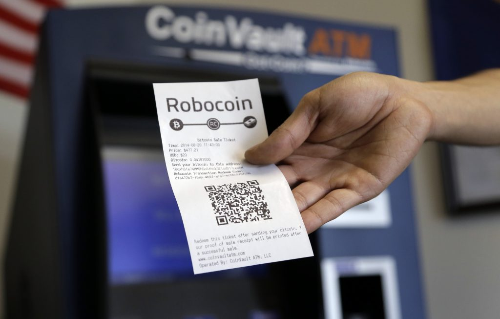 A consumer holds a receipt with a QR code after making a transaction at a bitcoin machine in Austin, Texas. (AP Photo/Eric Gay, File)