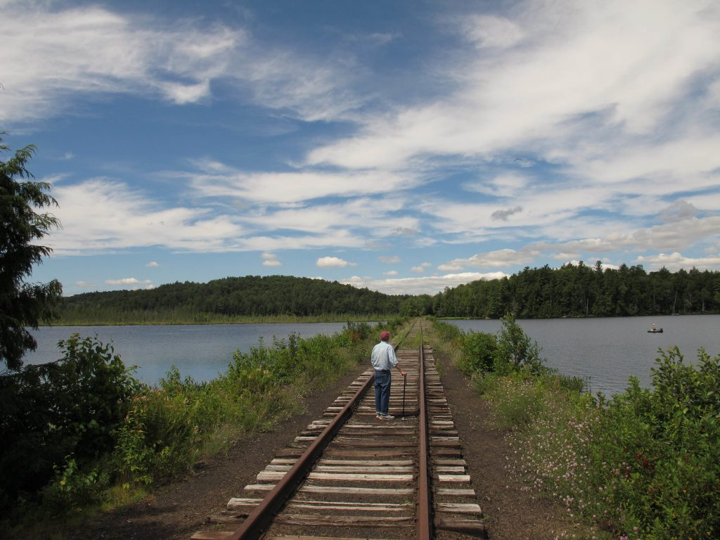 Dick Beamish, a member of the Adirondack Recreational Trail Advocates, stands in 2013 on deteriorating railroad tracks on a causeway across Lake Clear in Saranac Lake, N.Y. (AP Photo/Mary Esch, File)