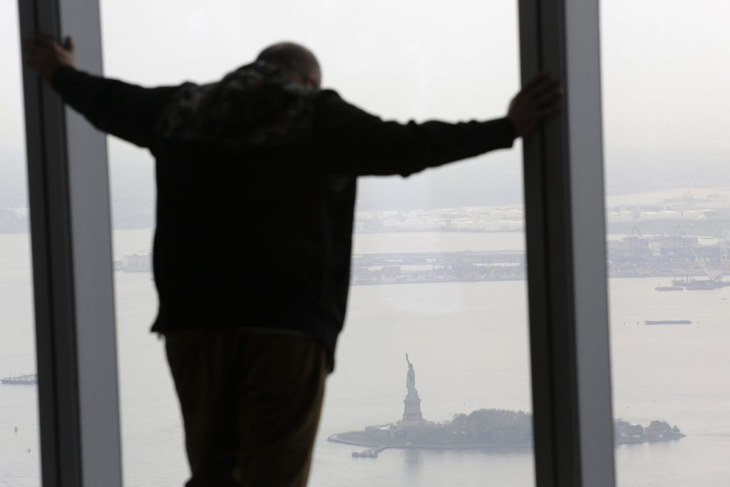 A man on Tuesday takes in a view of the Statue of Liberty from One World Observatory. (AP Photo/Mark Lennihan)