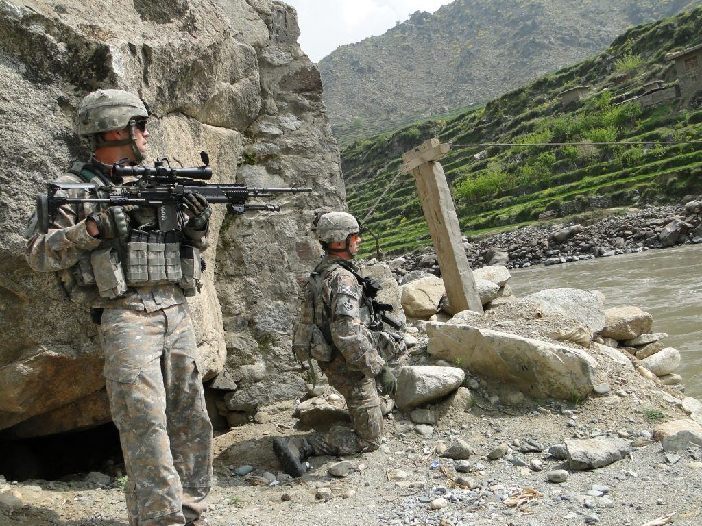 Sgt. Bradley Larson and First Lt. Andrew Bundermann, kneeling, lead a patrol into the mountains surrounding Saw village in eastern Afghanistan in March 2010. The two soldiers played critical roles in holding off a massive Taliban attack on Combat Outpost Keating six months earlier, in which eight U.S. soldiers and more than 75 Taliban members were killed. (Greg Jaffe/The Washington Post)