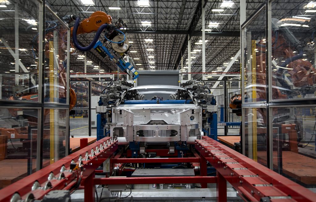 Robots rivet the side frame assembly on the body of a Revero electric car at the Karma Automotive factory in Moreno Valley, Calif. (Gina Ferazzi/Los Angeles Times/TNS)
