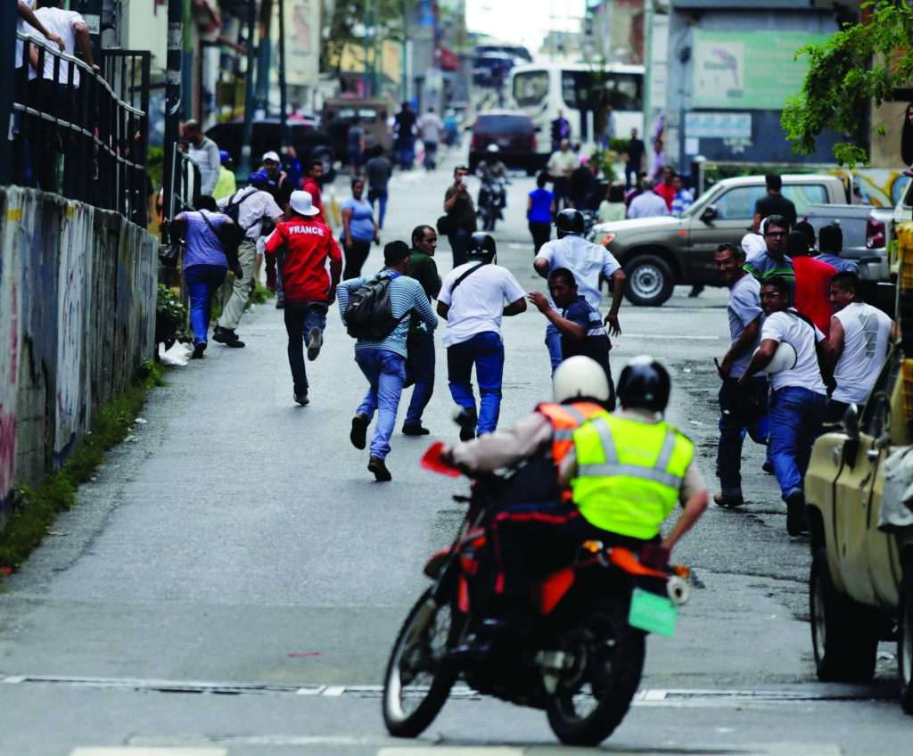 People run away from police (on motorcycle) during riots for food in Caracas, Venezuela, Thursday. (Marco Bello/Reuters)