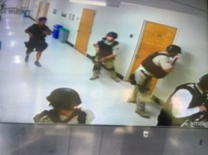 Police officers search corridors and rooms, in a still image from a CCTV camera. (Kara Leung/UCLA/Handout via Reuters)