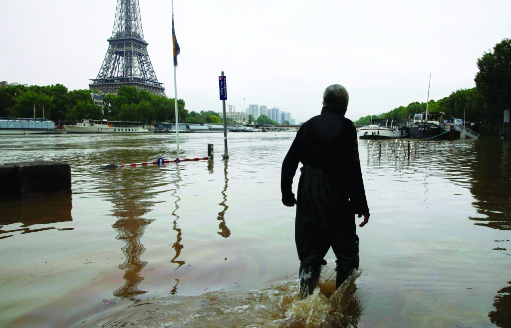 A man walks on a flooded road near his houseboat, moored near the Eiffel Tower, June 2, during flooding on the banks of the Seine River in Paris, France, after days of almost non-stop rain caused flooding in the country. (Pascal Rossignol/Reuters)