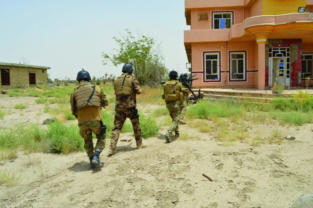 Armed Iraqi security forces personnel approach a house south ofFalluja, Iraq, on Monday. (Stringer/Reuters)