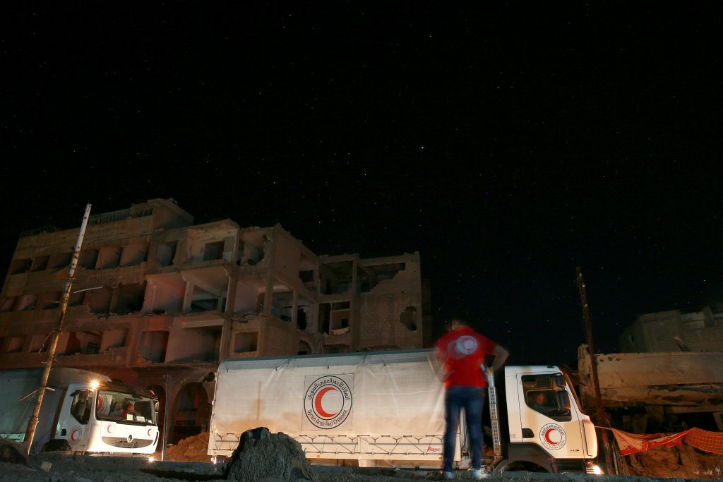 A Red Crescent and United Nations aid convoy carrying food aid unloads, in the rebel-held besieged town of Douma, eastern Damascus suburb of Ghouta, Syria, last week. (Reuters/Bassam Khabieh)