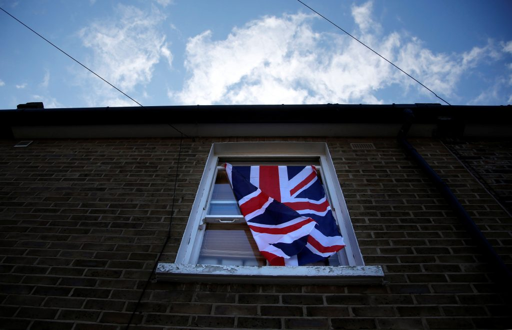 A British flag flutters in front of a window in London, Britain. (Reinhard Krause/Reuters)
