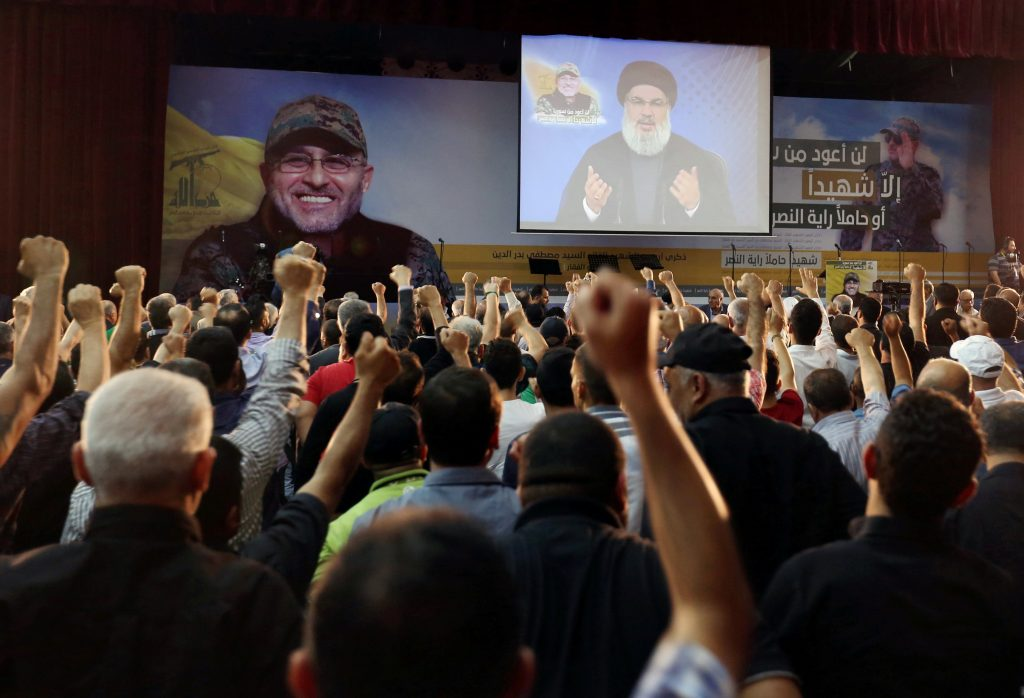 Hizbullah supporters in a Beirut suburb react as leader Hassan Nasrallah addresses them from a screen during a ceremony marking the 40th day after Hizbullah commander Mustafa Badreddine (picture on banner) was killed in an attack in Syria. (Reuters/Aziz Taher)