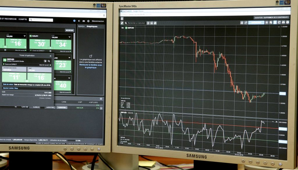 Screens, one which displays the rate of the British pound which drops against the US dollar (R) after the British referendum, are seen in a trading room in Paris, France, June 24, 2016. REUTERS/Jacky Naegelen