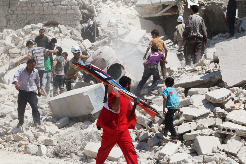 Civil defense members and civilians search for survivors at a site hit by an airstrike in the rebel-held area of Aleppo's al-Marjeh neighborhood on Sunday. (Reuters/Abdalrhman Ismail)