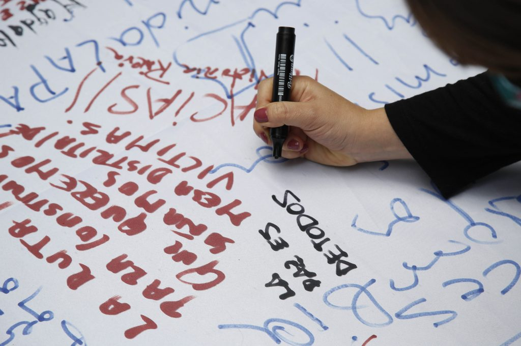 "A woman writes a message that reads in Spanish; ""Peace is for everyone"" as she waits to watch a live broadcast from Havana of the ceremony of the agreement between Colombian president and the head of FARC rebels on a cease-fire and rebel disarmament deal, in Bogota, Colombia. (AP Photo/Fernando Vergara)"