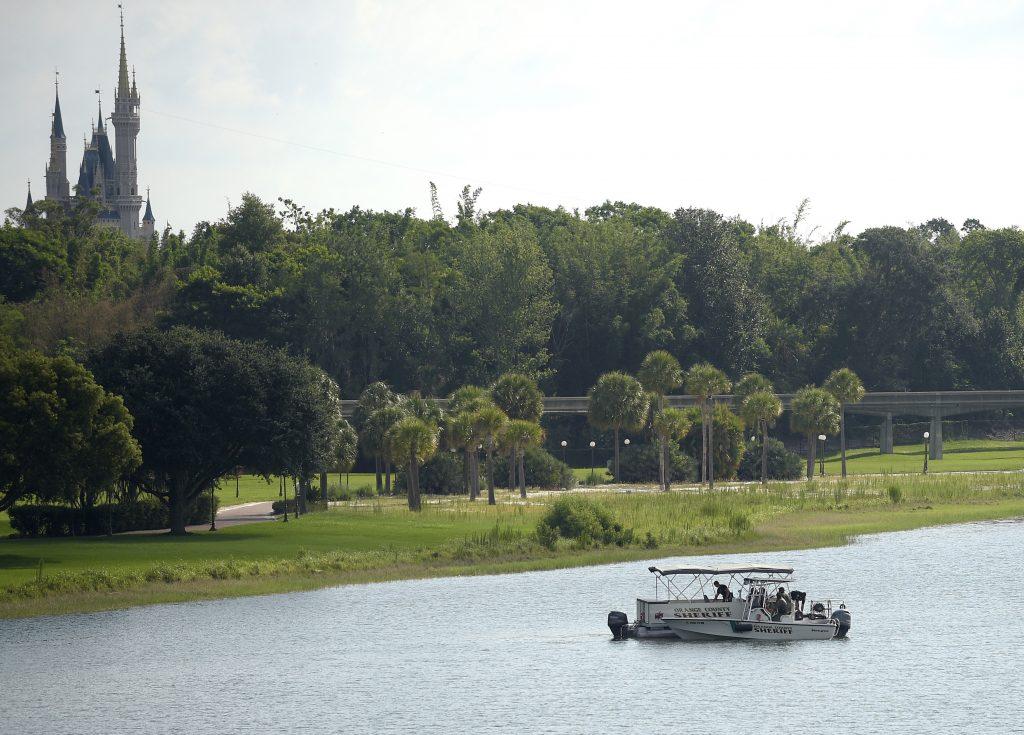 Orange County Sheriff's officers searching the Seven Seas Lagoon between Walt Disney World's Magic Kingdom theme park, left, and the Grand Floridian Resort & Spa in Lake Buena Vista, Fla., on Wednesday. (AP Photo/Phelan M. Ebenhack)