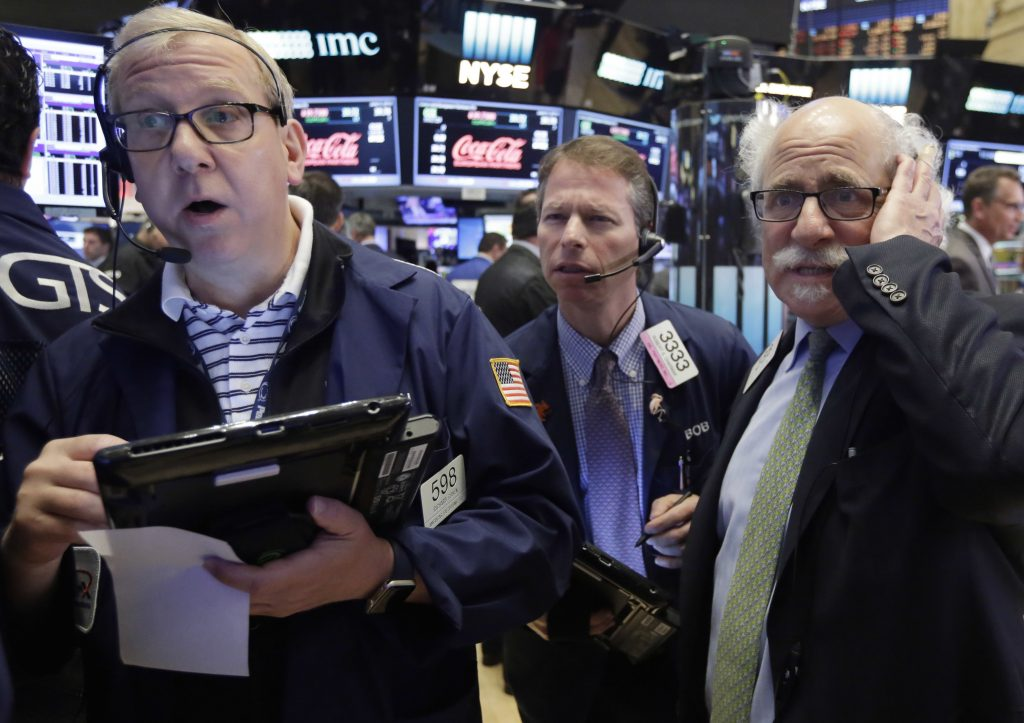 Traders Richard Cohen, left, Robert Charmak, center, and Peter Tuchman, work on the floor of the New York Stock Exchange on Friday. (AP Photo/Richard Drew)