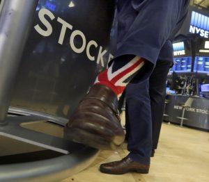 Specialist Michael Pistillo wears Union Jack socks as he works on the floor of the New York Stock Exchange on Friday. (AP Photo/Richard Drew)