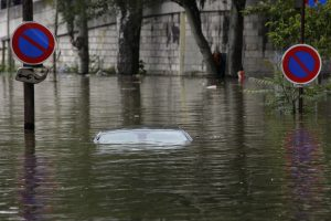 "The roof of a car parked in a marked ""no parking"" zone sticks out of the water on the flooded banks of the Seine river near the Eiffel tower in Paris, on Friday. (AP Photo/Jerome Delay)"