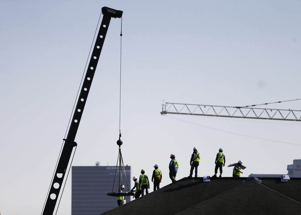 In this Wednesday, March 23, 2016, photo, construction workers unload supplies off a hoisted pallet on a rooftop in Atlanta. On Tuesday, June 7, 2016, the Labor Department issues revised data on productivity in the first quarter. (AP Photo/David Goldman)
