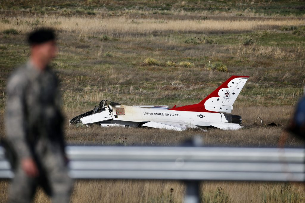 An Air Force security officer guards the site where a U.S. Air Force Thunderbird crashed following a flyover performance at a commencement for Air Force Academy cadets, south of Colorado Springs, Colo., Thursday, June 2, 2016. The pilot ejected safely from the jet. (AP Photo/Brennan Linsley)