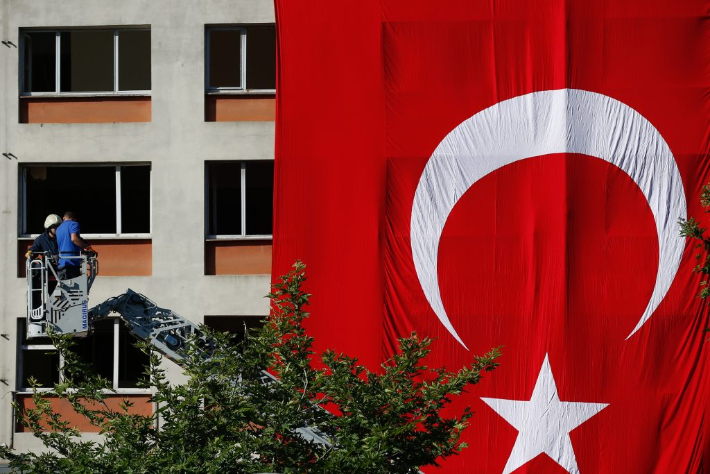 Workers drape a huge Turkish flag on a facade of a building damaged in Tuesday's explosion in Istanbul, Wednesday, June 8, 2016. The bomb attack that targeted a bus carrying riot police during rush hour traffic in Istanbul, killed a number of people and wounded dozens of others. It marks the fourth bombing to hit the Turkish city this year and there was no immediate responsibility claim but Turkey has witnessed an increase in violence linked to Kurdish rebels and Islamic State militants. (AP Photo/Emrah Gurel)
