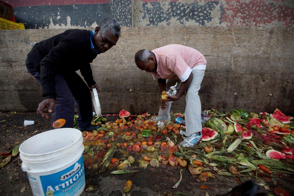 Pedro Hernandez, left, and his friend Luis Daza, pick up tomatoes from the trash area of the Coche public market in Caracas, Venezuela. (AP Photo/Fernando Llano)