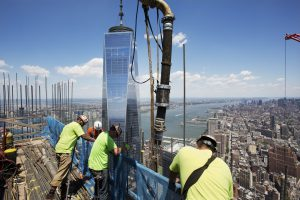 Workers guide a boom pouring concrete on top of 3 World Trade Center, on Wednesday. Behind them is One World Trade Center. (AP Photo/Mark Lennihan)