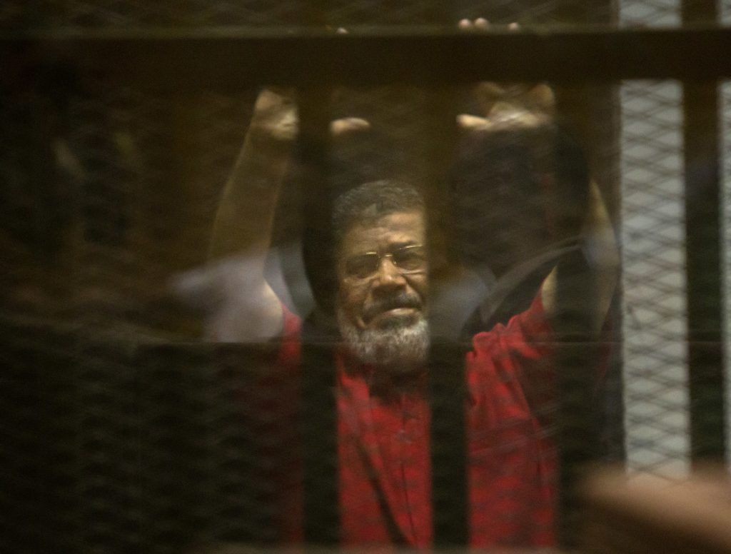 Former Egyptian President Mohammed Morsi, wearing a red jumpsuit that designates he has been sentenced to death, raises his hands inside a defendants cage in a makeshift courtroom at the national police academy, in an eastern suburb of Cairo, Egypt. (AP Photo/Amr Nabil)