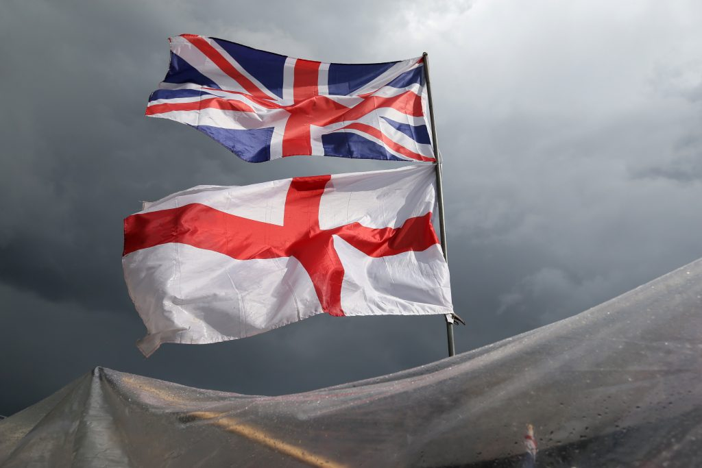 The flag of the United Kingdom of Great Britain and Northern Ireland, top, and the flag of England fly above a souvenir stand on Westminster Bridge. (AP Photo/Tim Ireland)