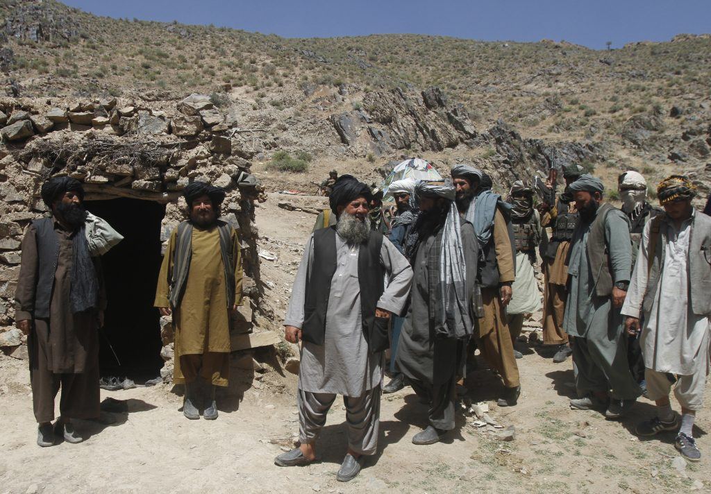 In this Friday, May 27, 2016 photo, Senior leader of a breakaway faction of the Taliban Mullah Abdul Manan Niazi, third left, arrives to give a speech to his fighters, in Shindand district of Herat province, Afghanistan. In the rugged terrain of the Taliban heartland in southern Afghanistan, the fight against Kabul has become a war for control of key stretches of main roads and highways as the insurgents use a new tactic to gain ground. (AP Photos/Allauddin Khan)