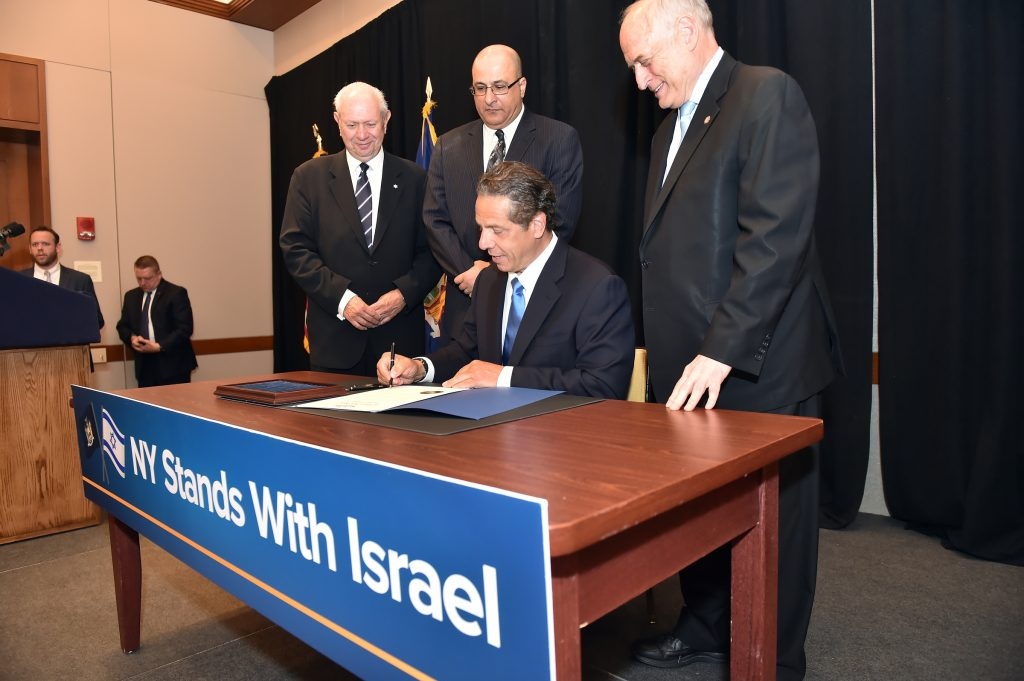 Gov. Andrew Cuomo on Sunday signs an executive order directing the divestment from public funds supporting the BDS campaign against Israel during a breakfast meeting at the Harvard Club. (Kevin P. Coughlin/Office of Governor Andrew M. Cuomo)