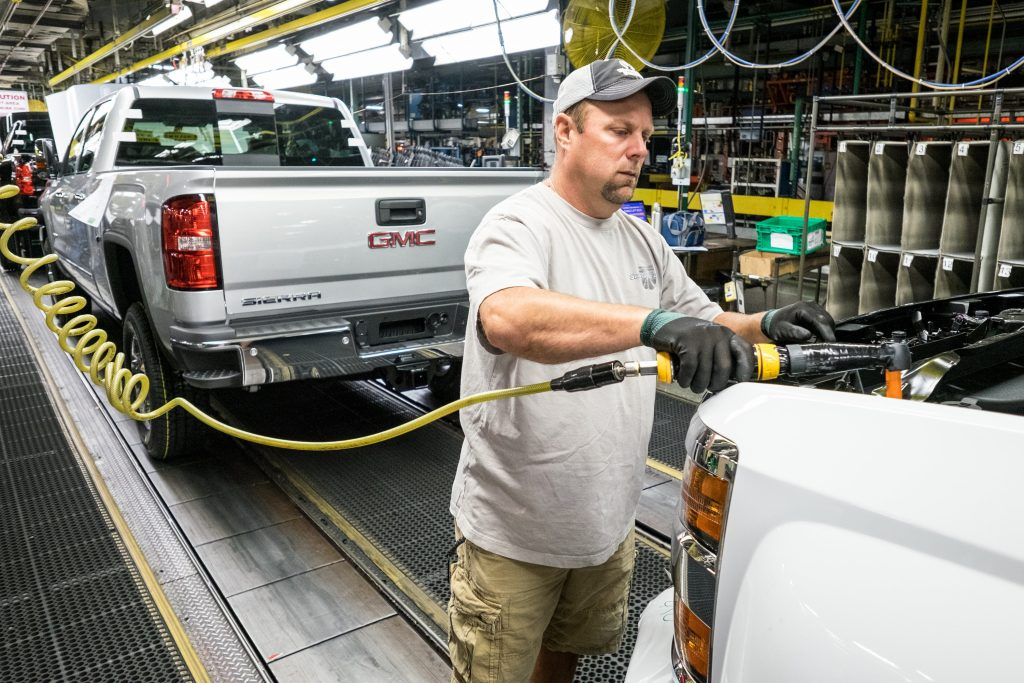 A GM employee attaches the grille to the front of a GMC Sierra truck in Flint, Mich. (Steve Fecht for General Motors)