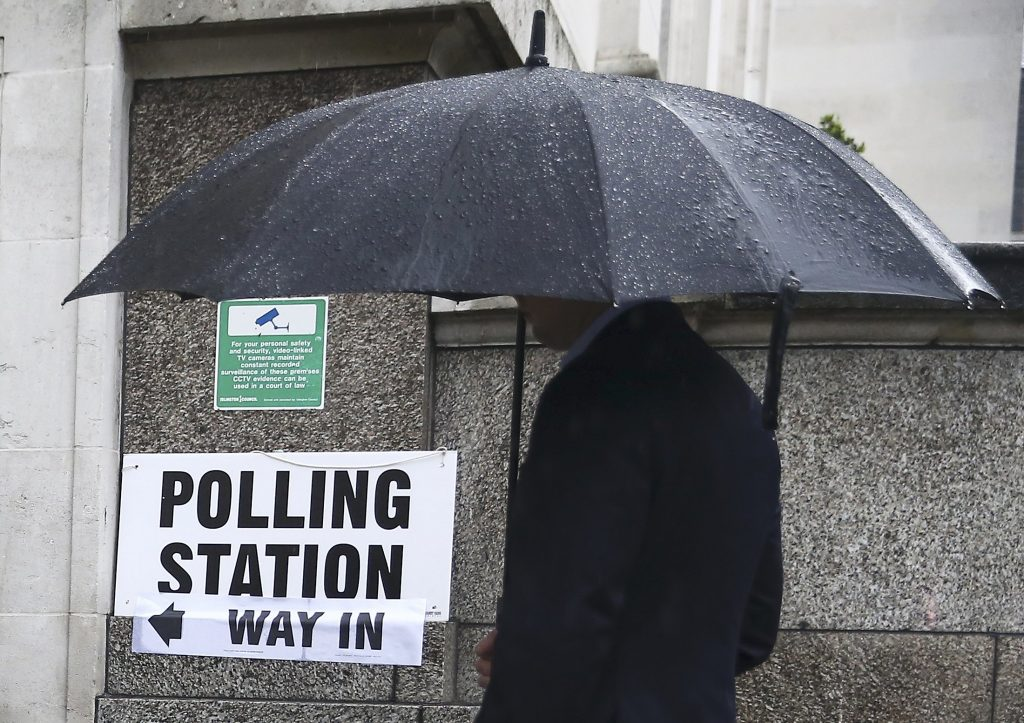 A man queues in the rain outside a polling station for the Referendum on the European Union in north London, Britain, June 23, 2016. REUTERS/Neil Hall