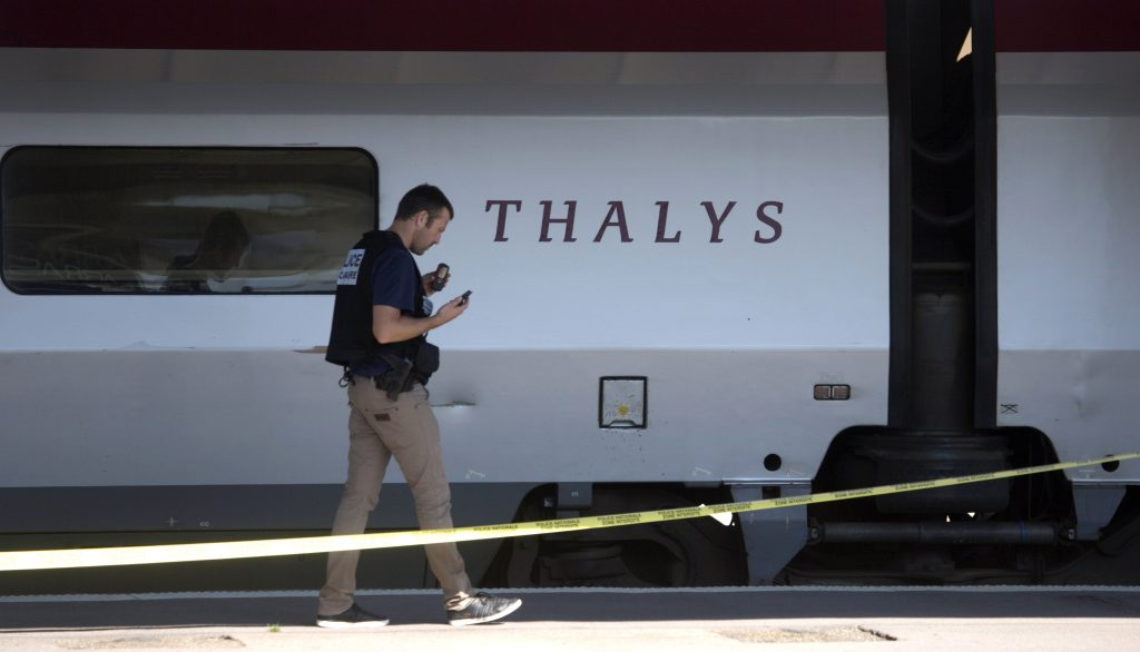 In this Aug. 22, 2015 photo, a police investigator walks next to a Thalys train on the platform at Arras train station, northern France. The Belgian Federal Prosecutor's Office on Monday, June 20, 2016 announced that six houses have been searched and six persons have been taken in for questioning in connection with the incident on the train on Aug. 21, 2015, in which a gunman prepared to open fire with an automatic weapon before being subdued by passengers. (AP Photo/Virginia Mayo, File)