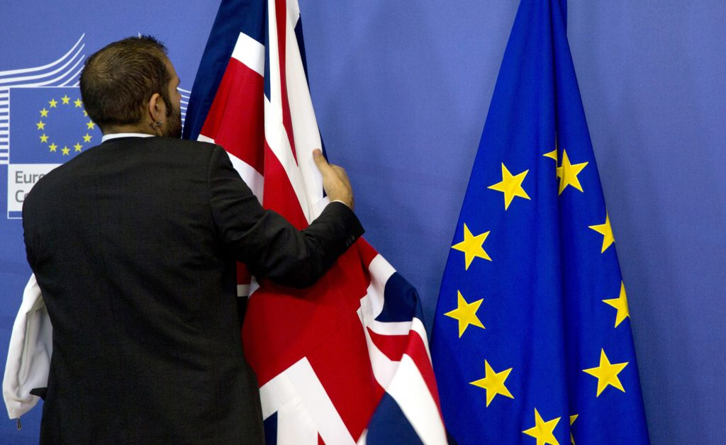 FILE- In this Oct. 15, 2015 file photo, a member of protocol adjusts the British and EU flags at EU headquarters in Brussels. As Britain prepares to vote whether to leave or stay in the European Union on June 23, 2016, goodwill between the continent and the island nation is fraying on both sides. (AP Photo/Virginia Mayo, File)