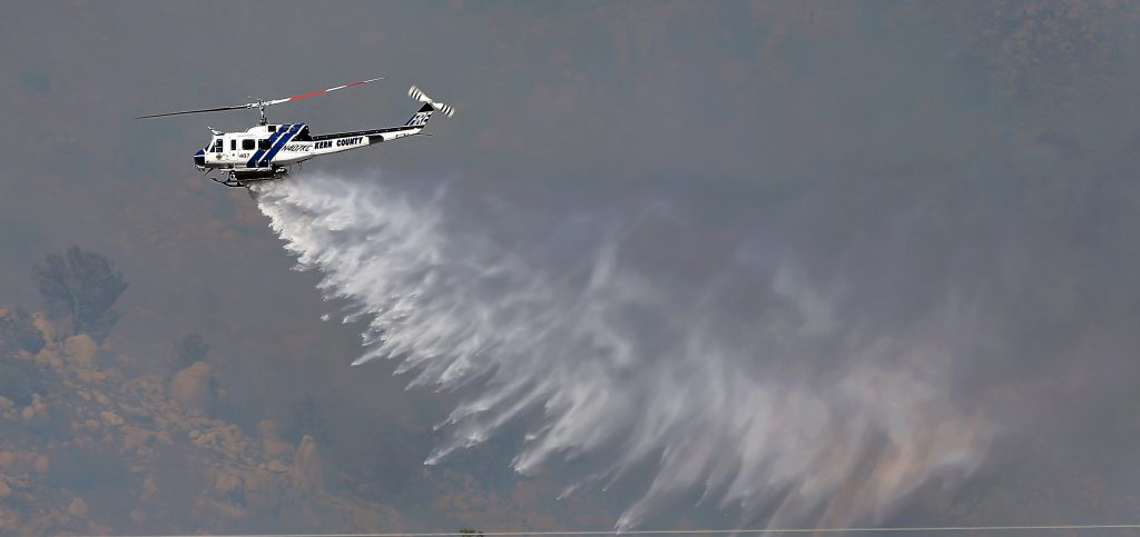 Kern County firefighting helicopter #407 makes a water drop on the Erskine Fire, Thursda, June 23, 2016 in Lake Isabella, Calif., The wildland fire moved quickly to several other small communities around the Kern River Valley burning several structures. (Casey Christie/The Bakersfield Californian via AP) MANDATORY CREDIT; MAGS OUT; NO SALES; ONLINE OUT; TV OUT