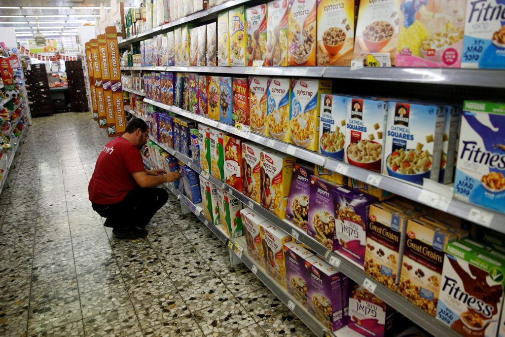 An employee arranges cereal boxes for sale at a supermarket in Yerushalayim. (Reuters/Ronen Zvulun)