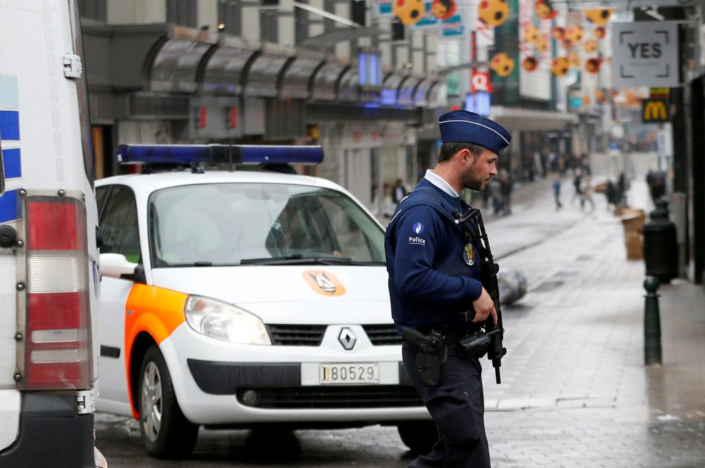 A Belgian police officer patrols near a central Brussels shopping centre after a man was arrested with hoax explosive belt, Belgium, June 21, 2016. REUTERS/Francois Lenoir