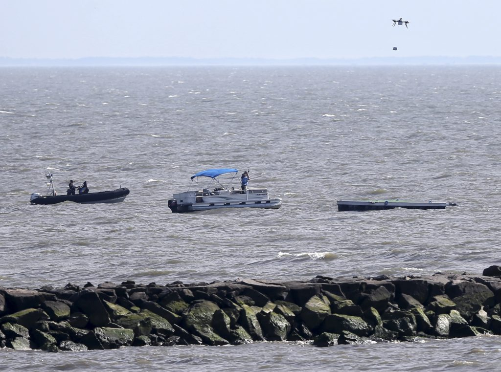 A drone on Wednesday lowers a payload of simulated blood onto a floating platform offshore during a delivery simulation in Lower Township, N.J. (AP Photo/Mel Evans)