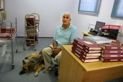 A man sits with his seeing eye dog at the Israeli Library for the blind. Photo by Chen Leopold/Flash 90.