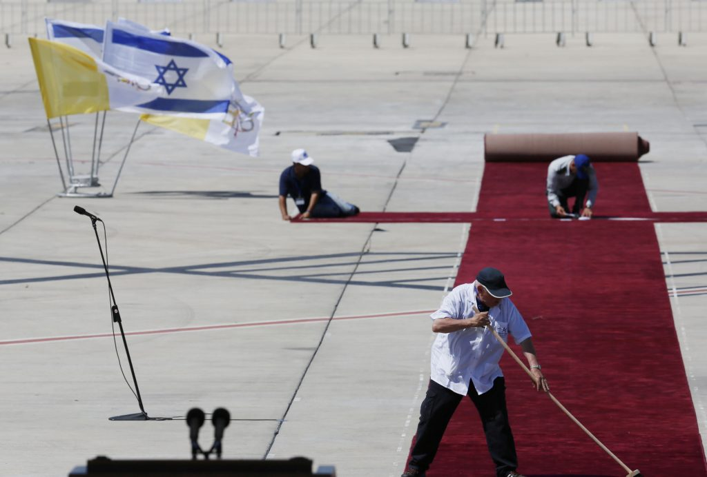 An Israeli worker cleans the red carpet at Ben Gurion airport. (Miriam Alster/Flash90)