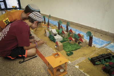 Young children build a model of settlements destroyed in Gush Katif, Gaza. Photo by Gershon Elinson/Flash90