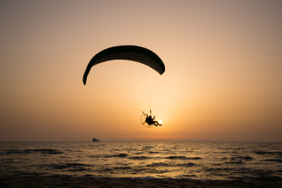 A paraglider flies through the sky over the sea at the beach in Ashkelon. Photo by Corinna Kern/Flash90