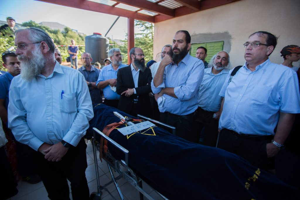 Friends and family members of Hallel Yaffa Ariel seen mourning near her body during her funeral in Kiryat Arba, Chevron. (Yonatan Sindel/Flash90)